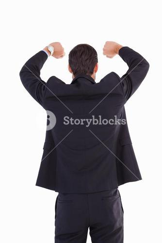 Rear view of businessman standing with arms raised