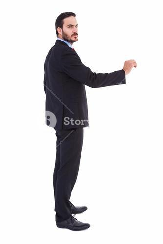 Serious businessman standing with arms raised