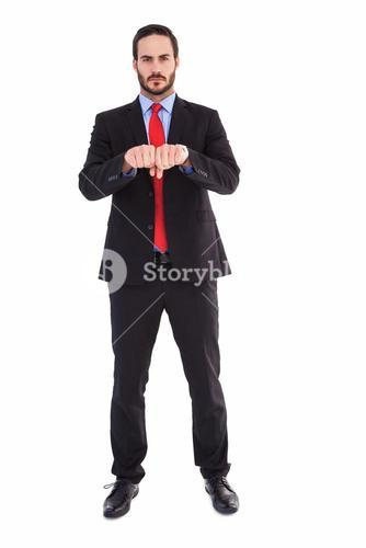 Unsmiling businessman with clenched fist in front of him