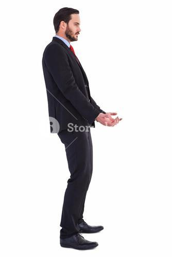 Unsmiling businessman holding something with his hands
