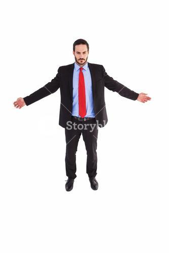 Unsmiling businessman standing with arms outstretched