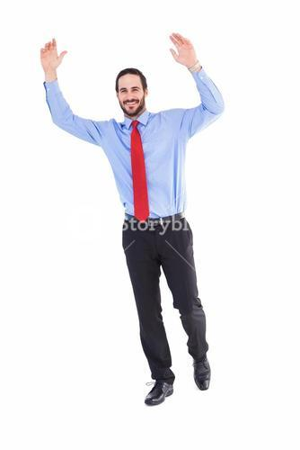 Smiling businessman stepping with hands raised