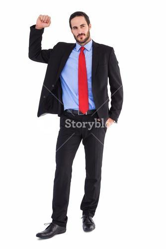 Unsmiling businessman standing with hand raised