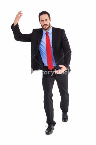 Unsmiling businessman holding something with hands