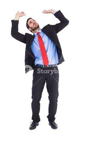 Worried businessman standing and pushing up