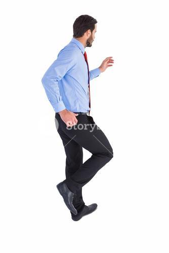 Unsmiling businessman in suit stepping