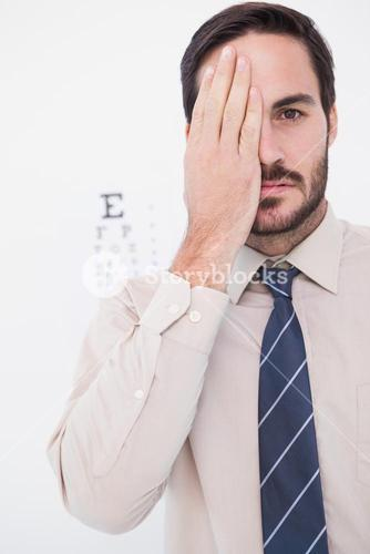 Unsmiling patient looking at camera with one eye