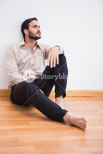 Casual thoughtful man leaning against wall looking up