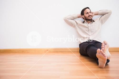 Thoughtful man leaning against wall with crossed arms