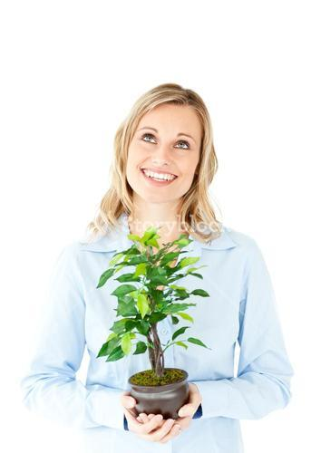 Portrait of a delighted businesswoman holding a plant