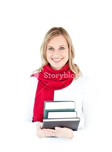 Portrait of a beautful woman with a red scarf holding books and smiling at the camera