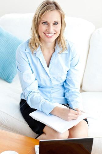 Radiant businesswoman writing in her notepad and using her laptop on a sofa