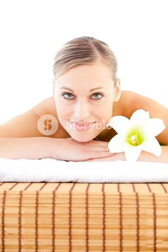 Close up of a radiant woman lying on a massage table with a flower