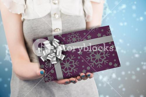Composite image of woman offering a wrapped gift