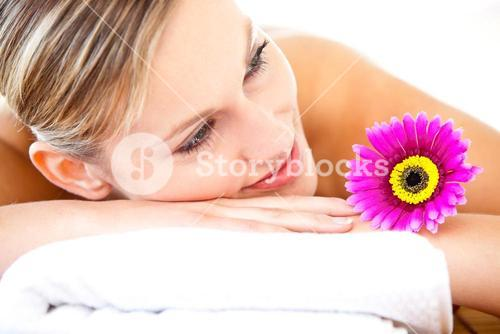 Close up of a bright woman lying on a massage table with a flower