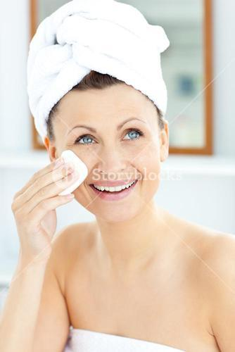 Smiling young woman with a towel putting cream on her face in the bathroom