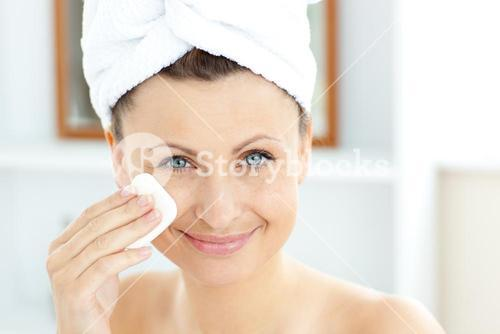 Joyful young woman with a towel putting cream on her face in the bathroom