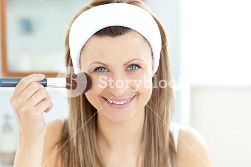 Smiling woman putting powder on her face smiling at the camera in the bathroom