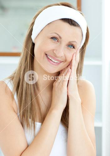 Smiling young woman putting cream on her face in the bathroom