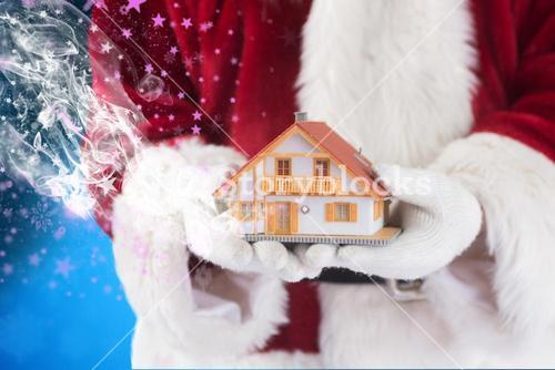 Composite image of santa holds a tiny house in his hands