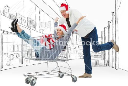 Composite image of man pushing wife in trolley with gifts