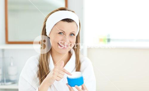 Delighted young woman putting cream on her face in the bathroom