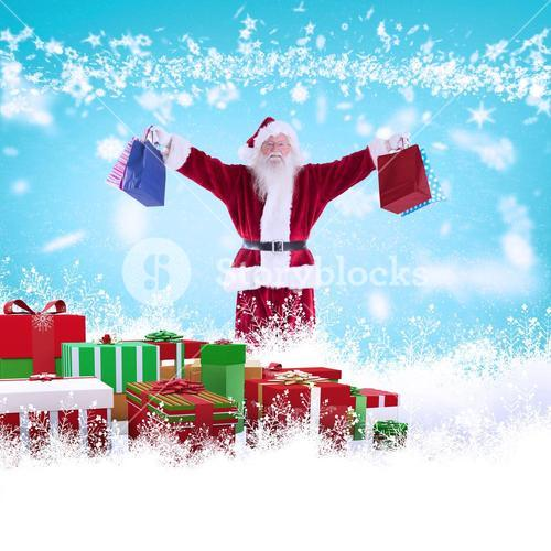 Composite image of santa holds some bags for chistmas