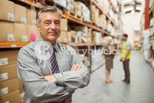 Smiling businessman with crossed arms
