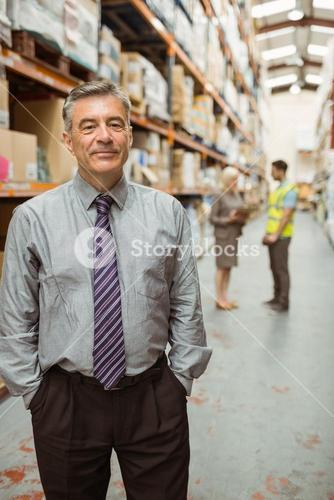 Cheerful businessman with hands in pocket posing
