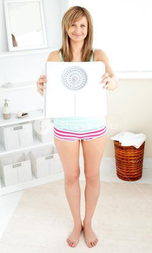 Smiling blonde woman holding a scale and looking at the camera in the bathroom