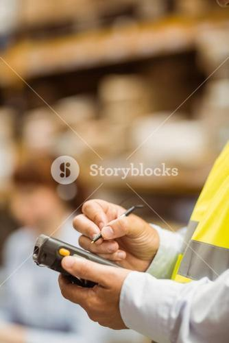 Close up of manager wearing yellow vest using handheld