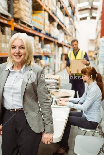 Smiling warehouse manager leaning on desk