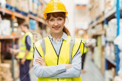 Warehouse manager smiling at camera with arms crossed