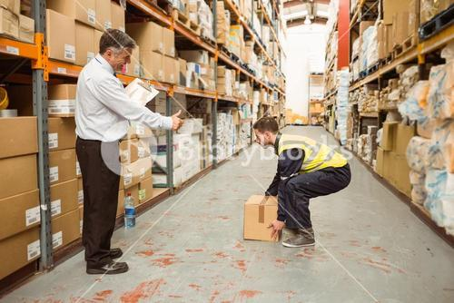 Manager watching worker carrying boxes