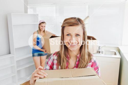 Two women carrying boxes at home