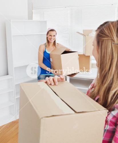 Two smiling women carrying boxes at home