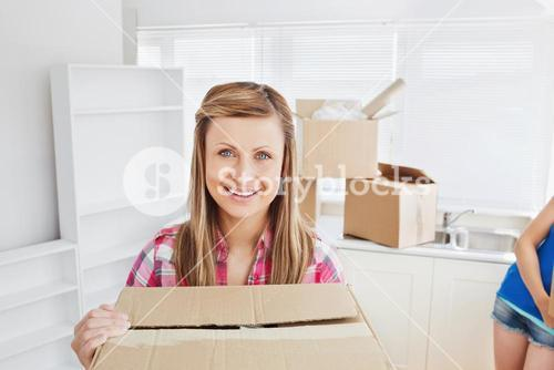 Bright woman carrying boxes at home