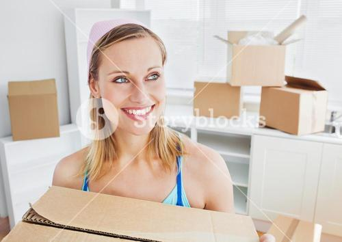 Positive woman carrying boxes at home