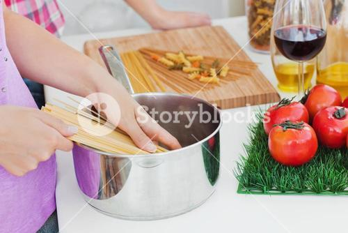 Close up of two women cooking spaghetti in the kitchen