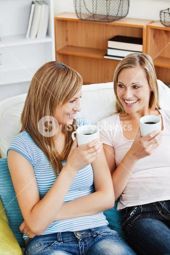 Two bright women drinking coffee together on a sofa