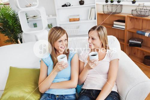 Two cute women drinking coffee together on a sofa