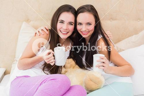 Pretty friends having coffee on bed