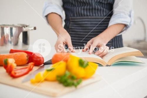 Woman following a recipe in book