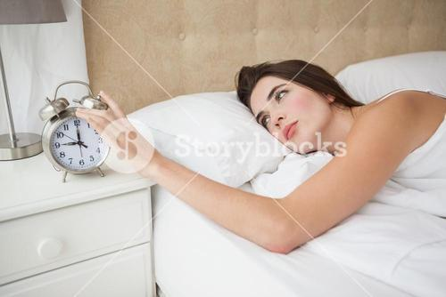 Pretty brunette turning off her alarm