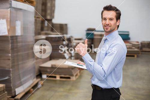 Warehouse manager smiling at camera showing thumbs up