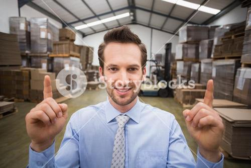 Smiling warehouse manager pointing up with finger