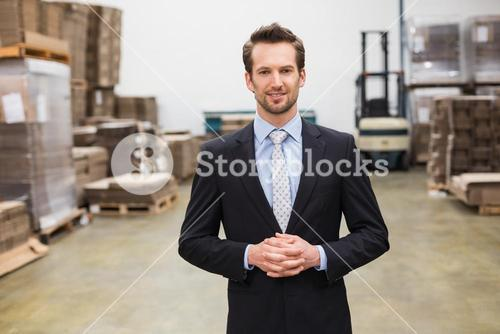 Warehouse manager standing hands together