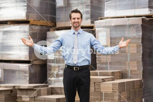 Smiling warehouse manager with hands out