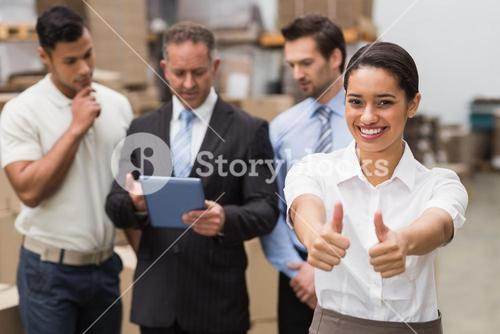 Manager showing thumbs up in front of her colleagues