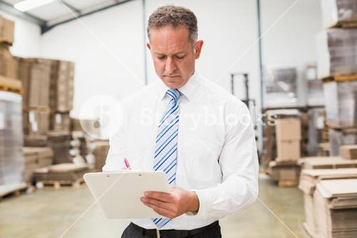 Serious boss writing on clipboard